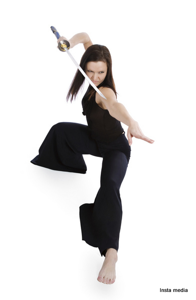 Beautiful woman in an aggressive posture with a sword