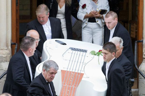 A giant, 12 ft guitar-shaped coffin, followed by his widow June Graham (white suit), is carried out of St Andrew's United Reformed Church at the funeral of musician John Graham