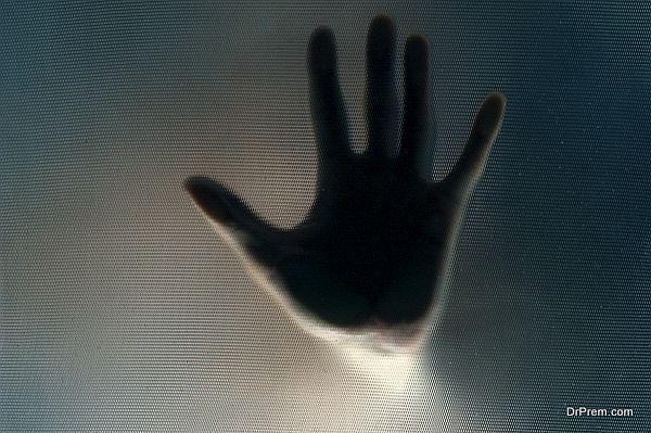 Hand through the semi-transparent glass